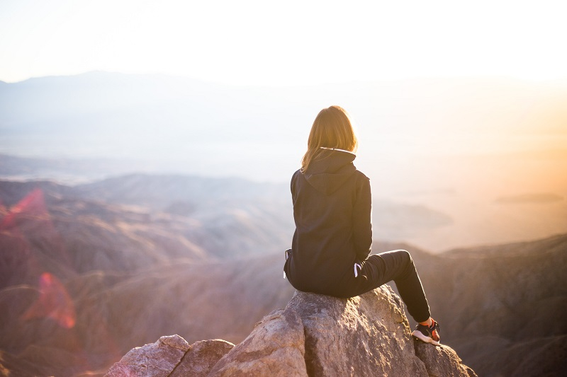 A woman sitting in the mountains with an amazing view