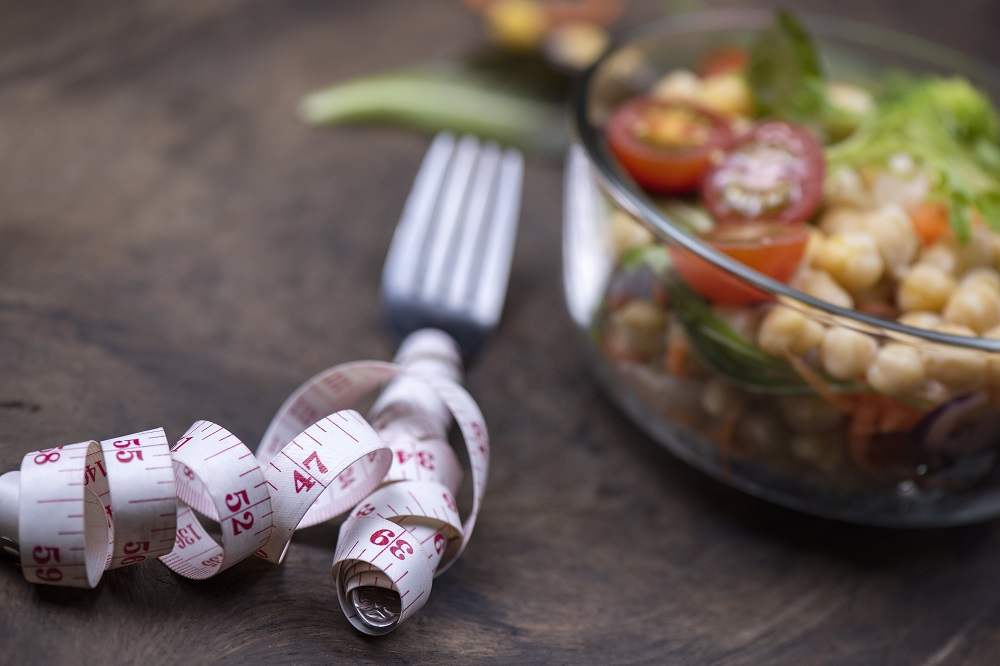 Measuring tape wrapped around fork next to a salad bowl