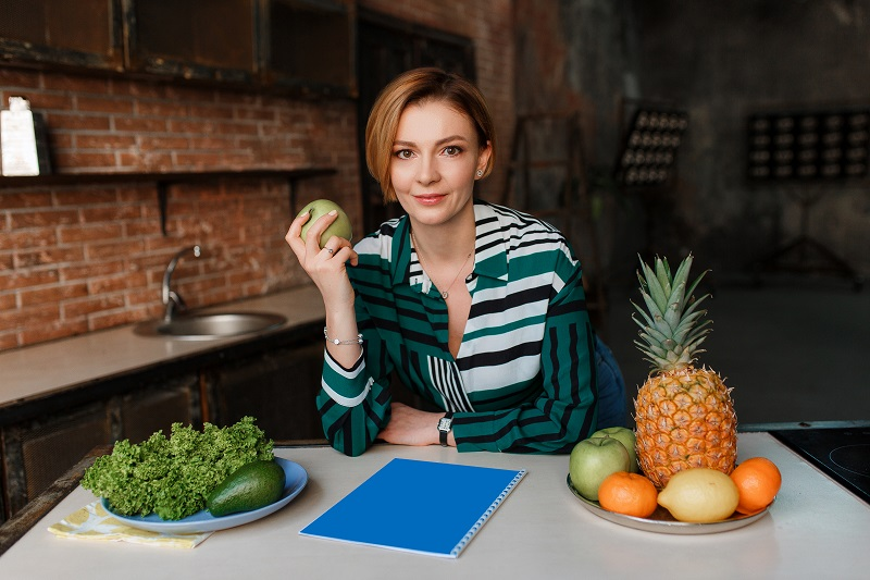 Woman in kitchen with healthy foods