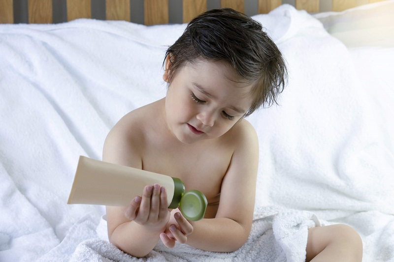 boy applying natural body lotion